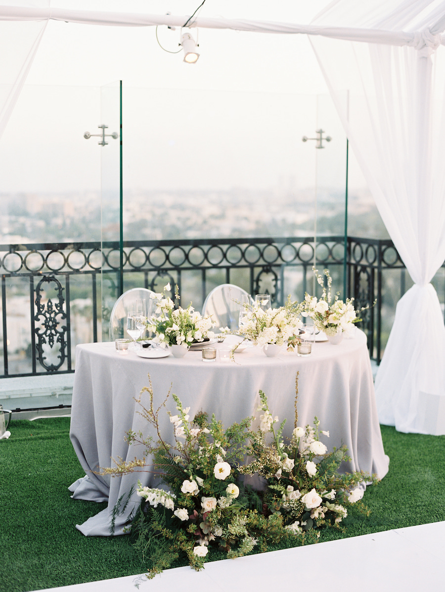 sweetheart table at wedding reception with white floral centerpieces