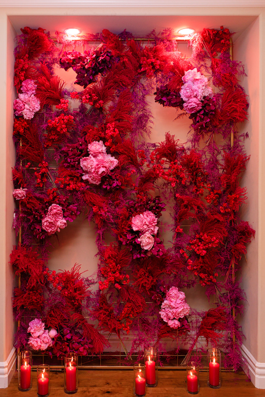 red and pink floral arrangements on wall with red lighting
