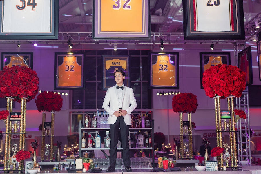 boy in white blazer posing with sports jerseys for bar mitzvah