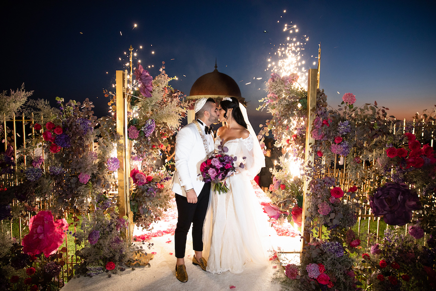 bride and groom kissing at wedding ceremony surrounded by floral displays