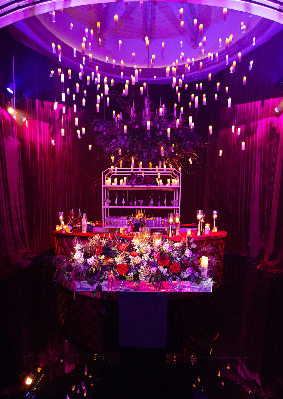 floral decorated bar area at wedding reception with floating candles and pink and purple lighting