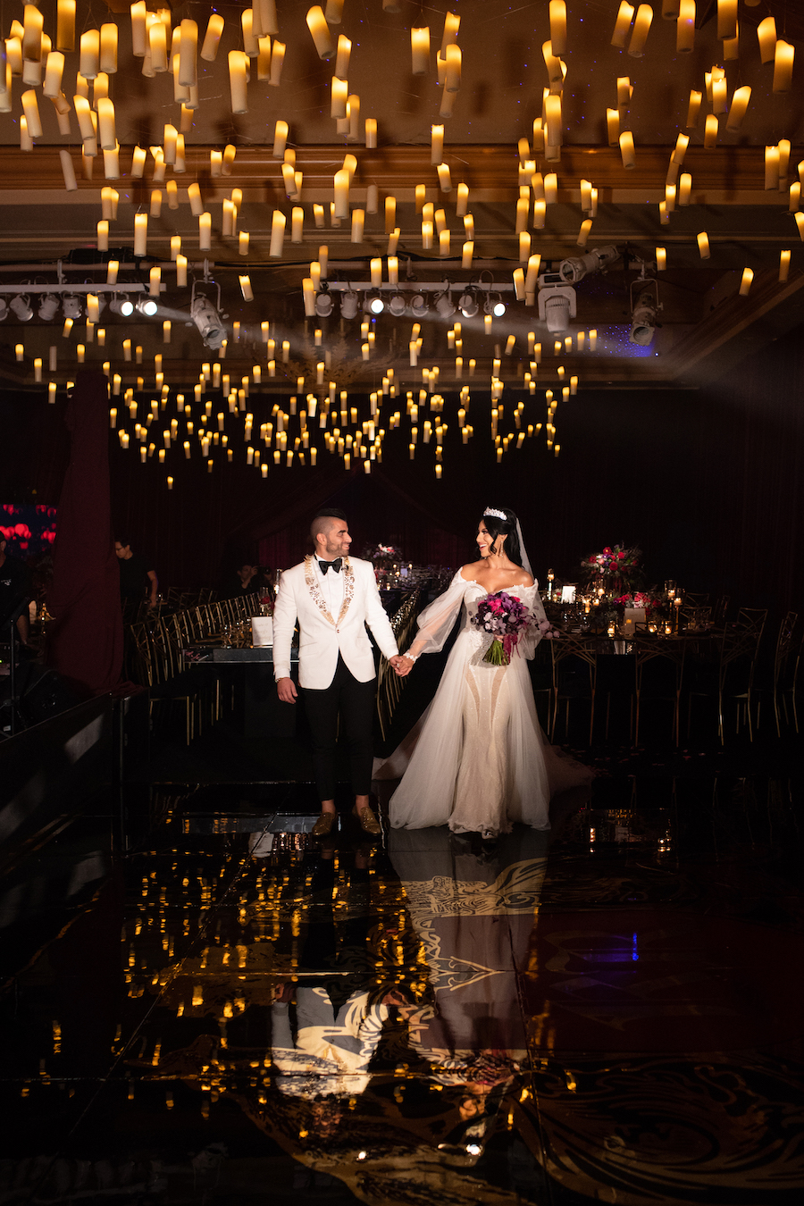 bride and groom on beautifully lit dance floor with floating candle lights