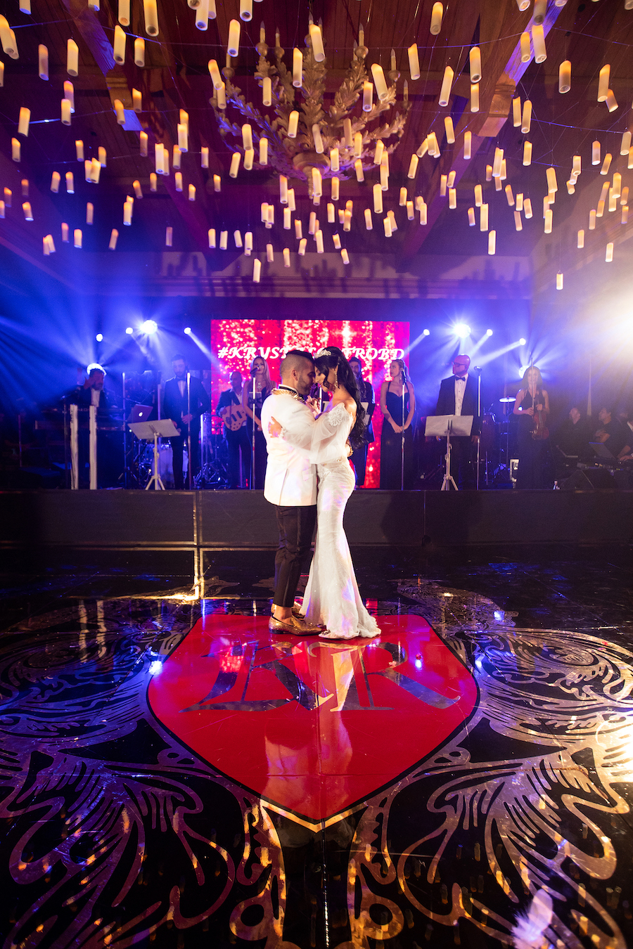 happy newlyweds having first dance on beautifully lit dance floor