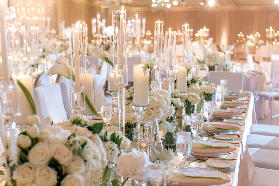 candlelight holders and white bouquets at wedding reception