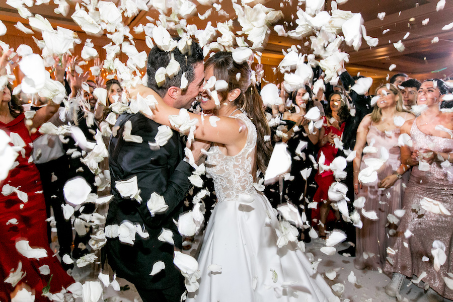 white rose petals showering newlyweds at wedding reception