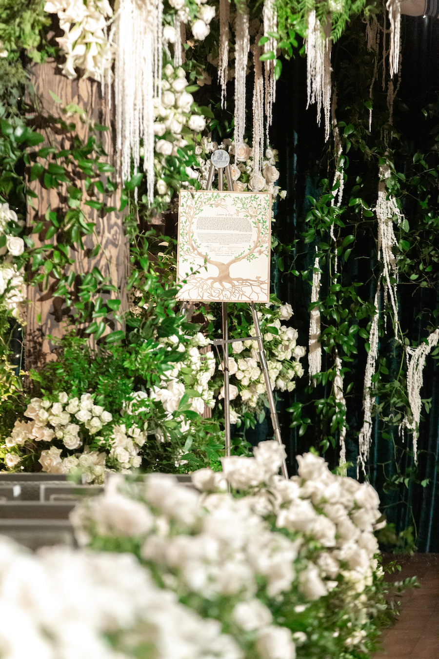 white roses and welcome sign at wedding ceremony