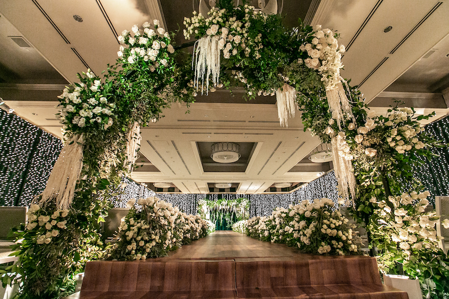 white floral arch filled with roses down the wedding aisle