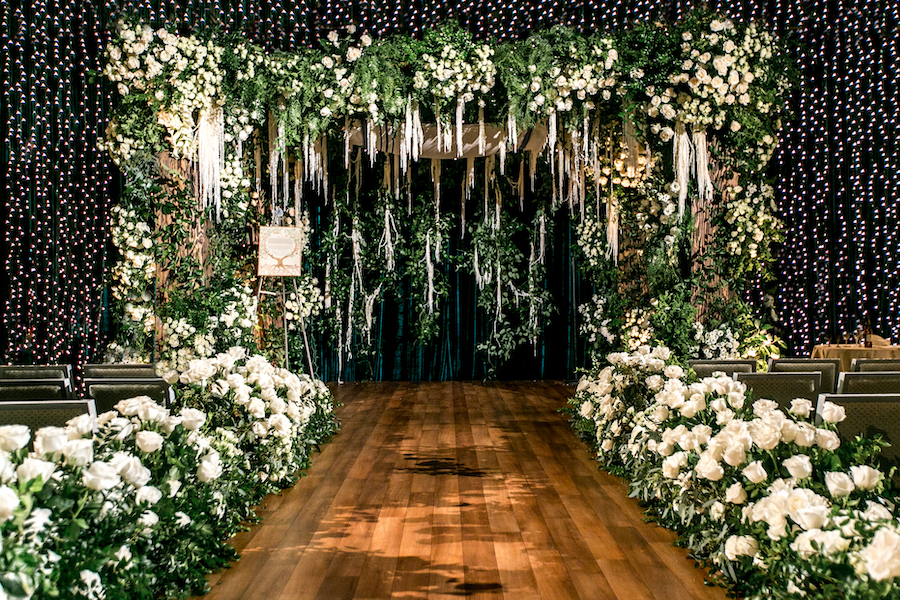 string lights and a large arch of white roses at wedding ceremony