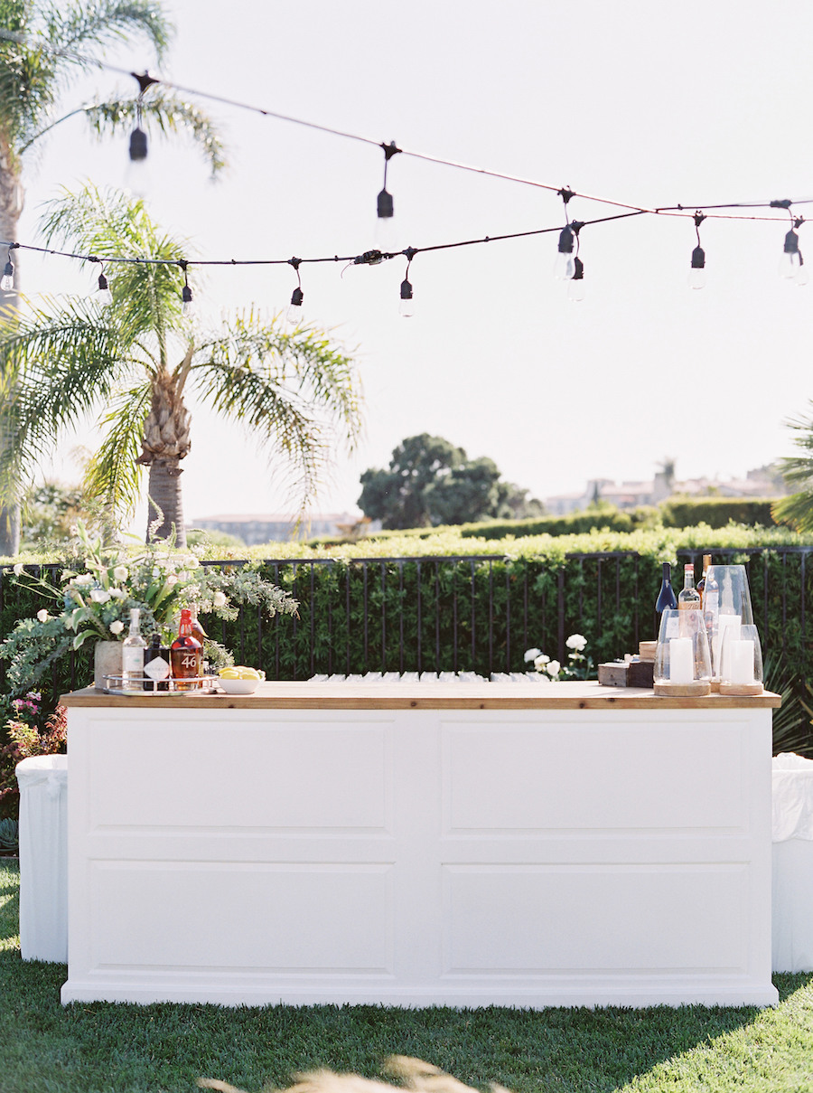 string lighting hung over bar at outdoor coastal wedding