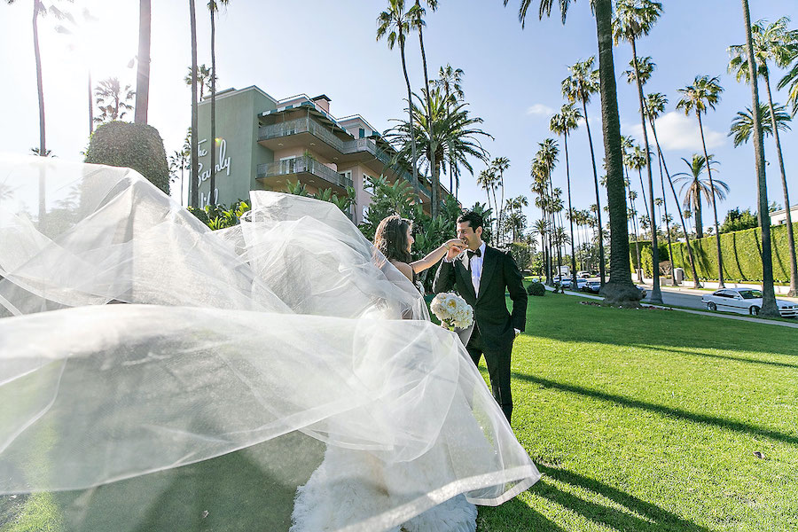 bride and groom in front of beverly hills hotel
